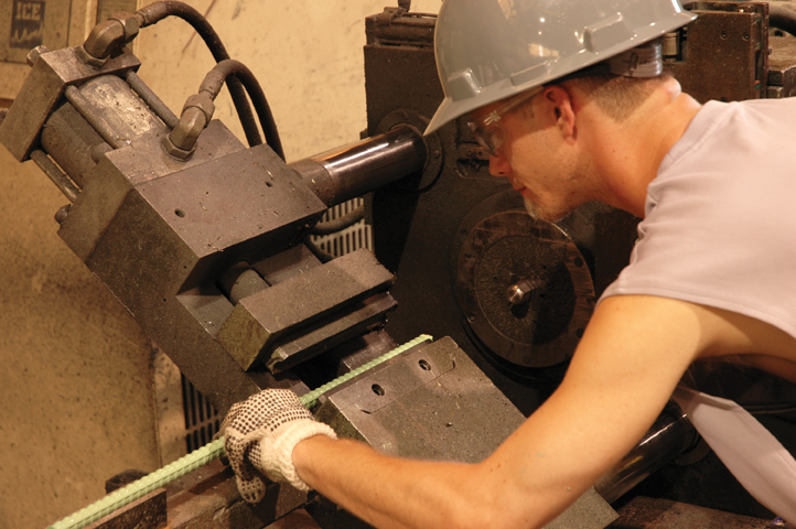 Factory image of man cutting rebar